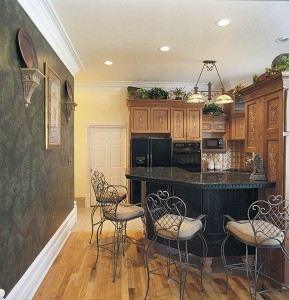 "The kitchen area continues the European theme, with a gargoyle on the counter and intricate detailing on the cabinet doors. ""I saw a bar on legs, and I just had to have it,"" Nikki says. The backsplash is brass and the countertop is Corian.The wood floor is ash."