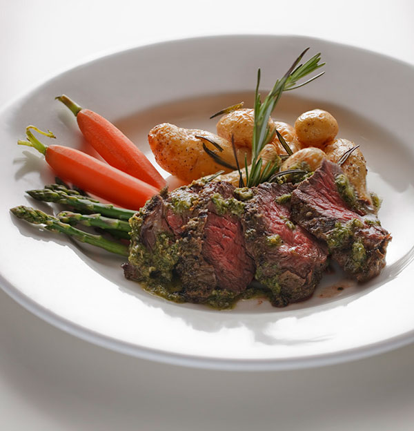 The hanger steak, prized for its rich, beefy flavor and tenderness, is marinated, grilled and served with seasonal chef's vegetables, roasted fingerling potatoes and a tangy herb chimichurri sauce.