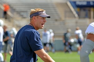 Head coach Bronco Mendenhall explains a drill to the team's linebackers.