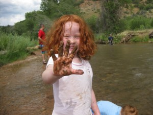 Delma Robison, 4, shows off her muddy hands while her brother, TJ Robison, 2, continues splashing in the water near Diamond Campground. In the background, their father, Jason Robison, is fishing while Brennen Robison, 11, looks on. (Photo courtesy of Jason Robison)