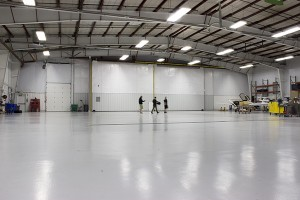 """Employees work to clear the airplane hangar for the ticket giveaway event tonight. """"Monster's, Inc."""" will be projected onto the hangar wall following the drawing. (Photo by Alisha Gallagher)"""