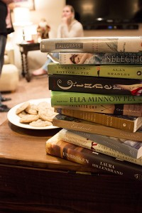 Rachel Davis sits in the background as she talks to a friend. The book club has read the pictured stack of books over the 18 months they have met together. (Photo by Alisha Gallagher)