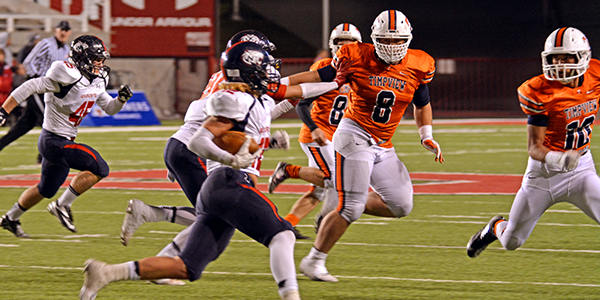 Max Anae (#8) and Isaiah Holloway (#10) tackle Woods Cross runningback Braxton Gunther (#12).