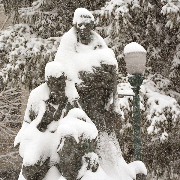 """This statue outside the Utah County Courthouse building titled """"The American Family"""" shows the depth of snow Utah County had received by mid-day."""