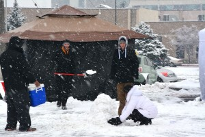 Michael Meier shovels snow as Jon Meier (right of Michael) looks on as their group tries to build a snow cow during one of Chick-fil-A's First 100 challenge. (Photo by Rebecca Lane)
