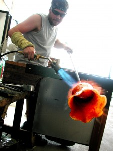 Treavor Holdman works on a glass blown bowl at Holdman Studios. Holdman is a key artist at Holdman Studios and is founder Tom Holdman's brother.