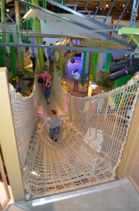 A boy walks across the rope bridge in the Rainforest exhibit on opening day of the Museum of Natural Curiostiy. (Photo by Rebecca Lane)