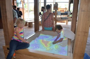 Kids manipulate the land to see where water would flow in a Water Works exhibit at the Museum of Natural Curiosity. (Photo by Rebecca Lane)