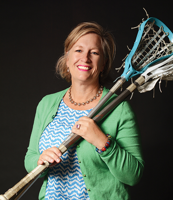 """Renee Tribe grew up as a tomboy in a house full of girls. She liked to skateboard, and most of her friends were boys. It wasn't until eighth grade that she thought, """"I should probably wear a dress — I don't look so bad in it."""" Now,  Renee is the co-founder of the GULL lacrosse league and the mother of four boys and one girl. (Photo by Dave Blackhurst)"""