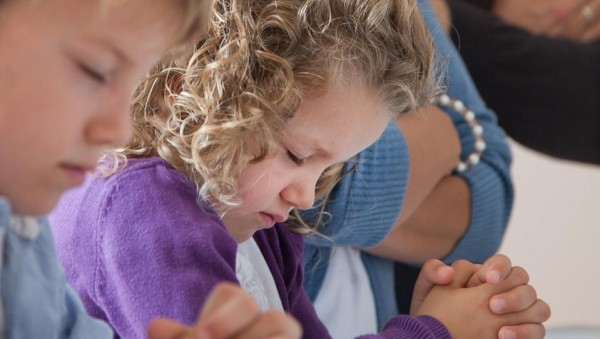 Family prayer and scripture study can help ground children spiritually, even when things are changing outside the home. (Photo courtesy Mormon Newsroom.)