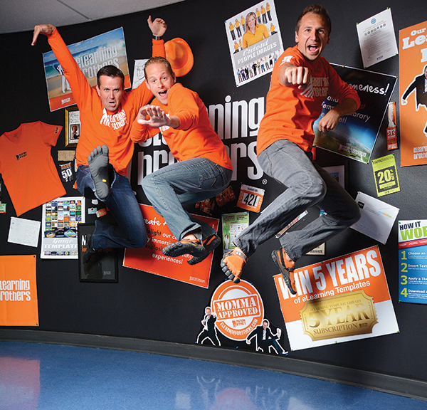 """NEW HEIGHTS. As part of a marketing tradition, the eLearning team has hundreds of pictures with clients striking nijna poses. """"You'd be surprised at how often adults want to ninja pose with us,"""" says Andrew Scivally, center. """"And they are good at it."""" Also pictured: Curtis Morley (left) and Shawn Scivally. (Photo by Dave Blackhurst)"""