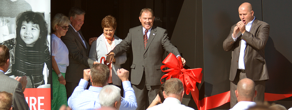 Utah governor Gary Herbert cuts a ceremonial reb ribbon making Blendtec's new plant official.