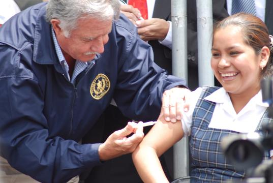 Former President Óscar Berger of Guatemala gives the first immunization shot to a local school student. (Photo courtesy Mormon Newsroom.)