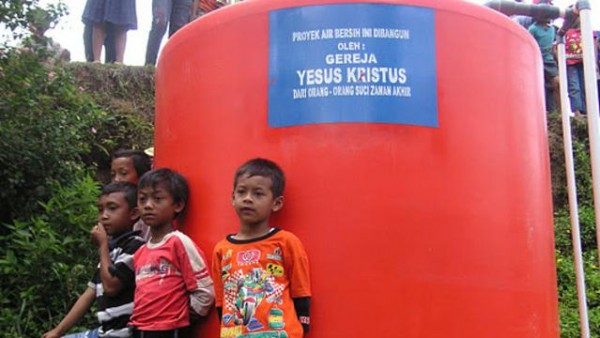 Local boys pose next to a tank of fresh water, which is flowing for the first time to villages in Indonesia thanks to LDS Church humanitarian aid. (Photo courtesy Mormon Newsroom.)