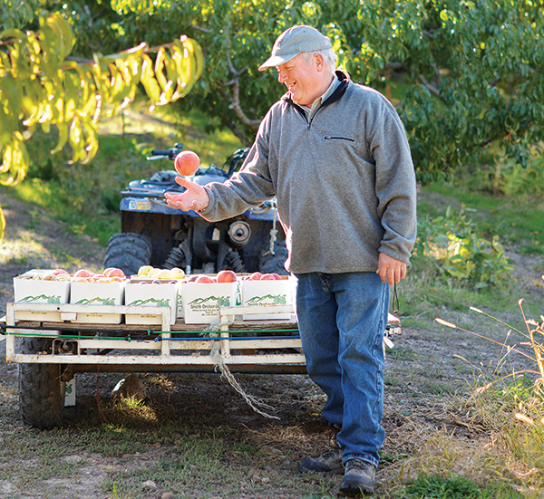 """Scott Smith, owner of Smith Orchards, says he wants to farm 'til the day he dies. """"I want to go with my boots still on,"""" Scott says. (Photo by Leah Aldous)"""