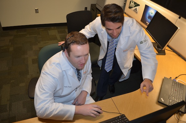 UVU SMARTLab assistants Nathan Pearson and Josh Groves work with some of the new equipment UVU received for market research. (Photo by Rebecca Lane)