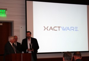 Commissioner Larry Ellertson presents Jim Loveland, with Xactware, the Business of the Year Award. (Photo by Candi Higley)