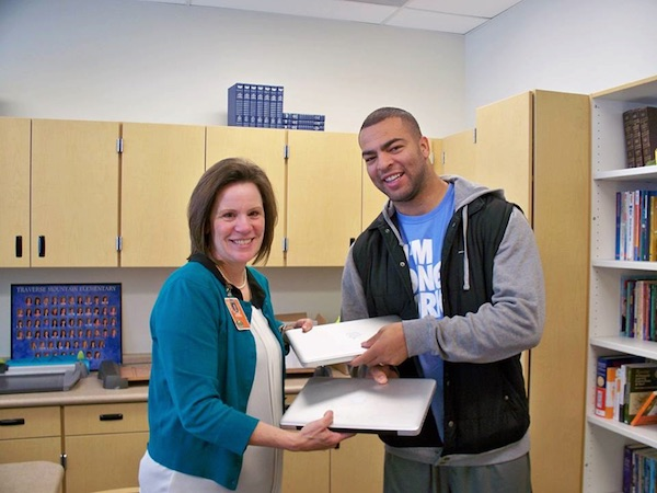 Ilene Strong, Traverse Mountain Elementary's principal, switch back laptops with former BYU linebacker Kyle Van Noy. (Photo courtesy Alpine School District)