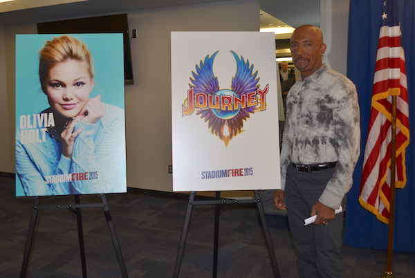 Montel Williams, who will emcee for the 2015 Stadium of Fire, stands next to the posters announcing the performers (Journey and Olivia Holt) for this year's show. (Photo by Rebecca Lane)