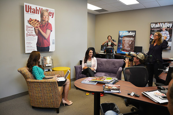 """Kim Christensen, a UtahValley360.com and Utah Valley Magazine writer, interviews McKenzie Deakins, a Utah Valley photography, at Bennett Communications for """"House Hunters."""" Ironically, the film crew had to create an interview space in our advertising room, which meant taking furniture from different parts of the office."""
