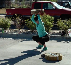 Kristen Crafts does squats with a hose over her head at Lehi Fire Departments event workout like a firefighter event. (Photo courtesy Lehi Fire Department)