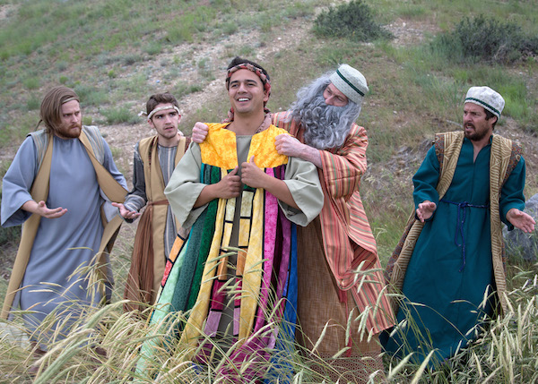 Corey Morris is Joseph (colored coat); Andy Kelson is Jacob (full gray beard and staff); Eric Smith is Reuben (light purplish costume and in some photos he has a greenish headpiece and in some just dark blonde longer hair); Brad Martin is Issachar (off white hat and bluish/green costume); and Stephen Brailsford is Zebulon (rope headband/striped costume).  (Photo by Mark A. Philbrick)