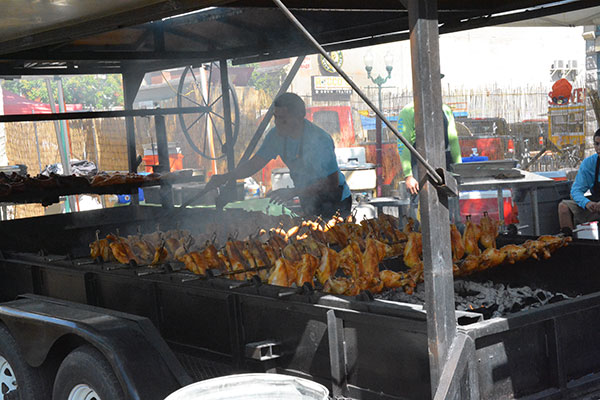 A worker roasts chicken at the Freedom Festival. There are many food vendors in downtown Provo for Freedom Fest. (Photo by Rebecca Lane)