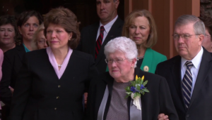 Donna Packer (center) watches as President Packer's casket is lifted into  the hearse.