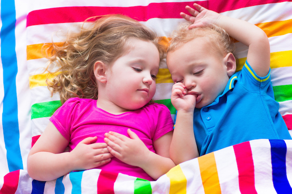 Two kids sleeping in bed under colorful blanket. Children relaxing in bedroom. Tired toddler girl and baby boy before bedtime. Rainbow textile bedding for nursery. Brother and sister play at home.