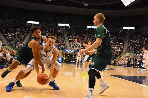 BYU's Kyle Collinsworth and UVU's Telly Davenport fight for possession of the ball. Collinsworth had 17 points, 9 rebounds and 7 assists. Davenport had 3 points, 5 rebounds and 3 assists. (Photo by Rebecca Lane)