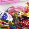 Children's toys and items of clothing strewn on floor near open cupboard door in bedroom
