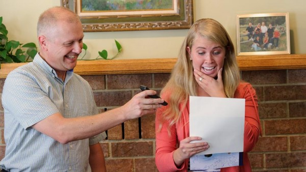 Newly called missionary Alli Wright reads her mission call while standing with her father, Russ. (Photo courtesy Mormon Newsroom.)
