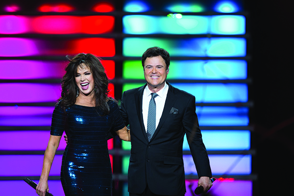 "Donny and Marie have crooned, cackled and danced alongside each other their whole lives. The two siblings are in their eighth year of performing together five nights a week at The Flamingo in Las Vegas. They have a template for their show each night, but 50 percent of the show is ad lib, including spontaneous audience interaction and playful sibling rivalry — especially when joking about ""Dancing With the Stars,"" which Donny won. (Photo courtesy Caesars Entertainment)"