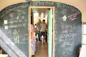 The Adventure Bus crew has left its mark on the blackboard as well as the lives of the Stauffers. Each of the eight crew members has a name — and interest — in the adventure venture. (Photo by Alisha Gallagher)