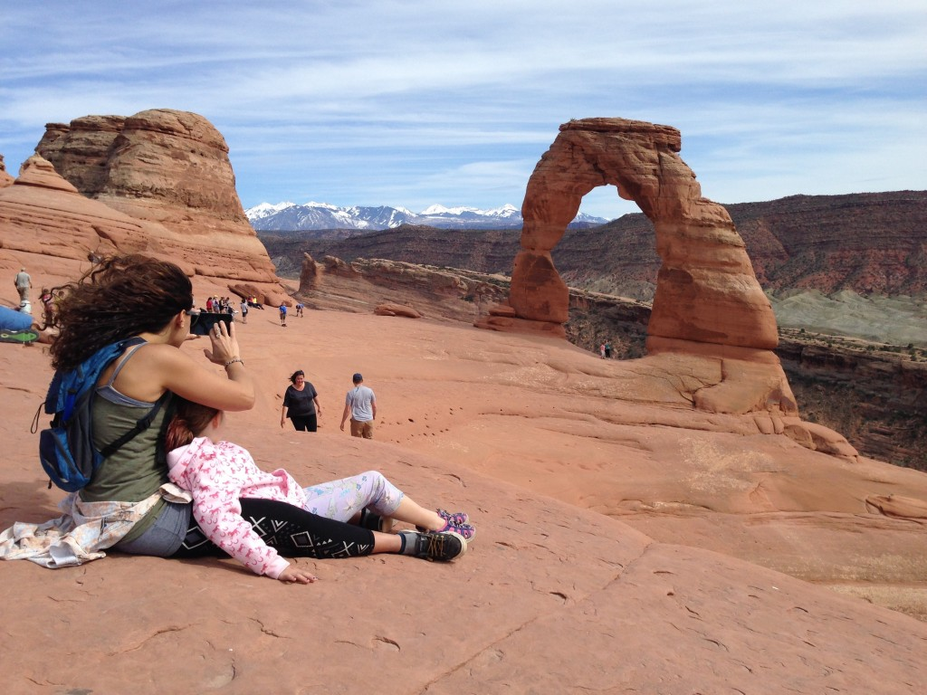 Hikers take in the view of Delicate Arch, one of Utah's most famous landmarks, while visiting Arches National Park. (Photo by Camden Ball)