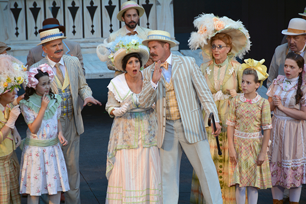 "Gregory Hansen (Harold Hill), center, warns the citizens of River City, Iowa of the ""trouble"" they are in because of their new pool table at the Sundance Theatre's production of ""The Music Man."" (Photo by Rebecca Lane)"