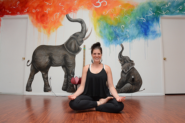 "Brittany Andrews bent over backwards to build her budding yoga studio, The Yoga Underground, in Provo. She worked as a yoga instructor and restaurant server for up to 60 hours a week for five years straight — and it paid off. Now that her restaurant days are over, dozens of yogis flock to her studio every day. ""It's like there's magic to yoga,"" Brittany says. ""There'a a reason people come here versus going to the gym, even if they can't articulate it."" (Photo by Alisha Gallagher/UV Mag)"