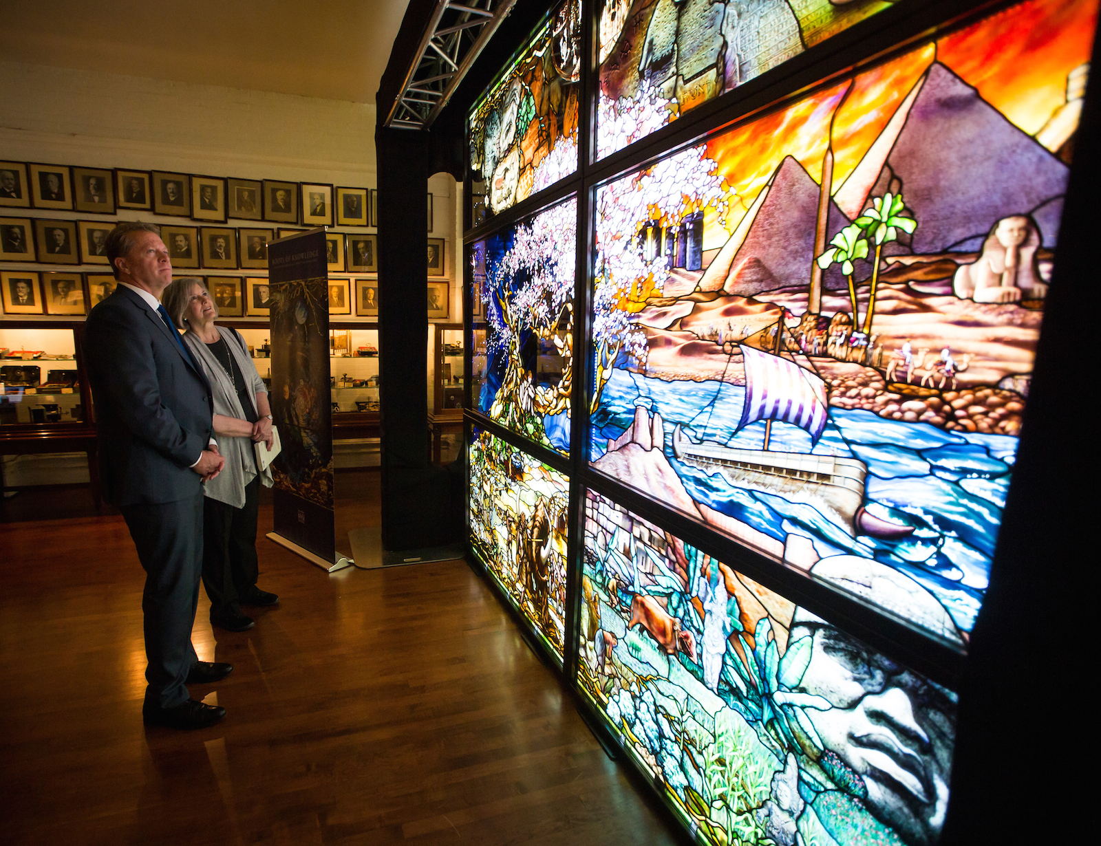"""Lecture attendees examine panels from """"Roots of Knowledge,"""" a stained glass exhibit headed for a permanent home at UVU Library, while on display in Manhattan this week. (Photo courtesy of UVU Marketing)"""
