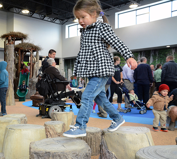 Anna Cantor, 3, jumps between logs during the grand opening of The Orchard at University Place. (Photo by Rebecca Lane)
