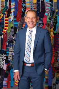 "Although John likes the high quality of Stance socks, he gives a lot of pairs away and looks for lower-priced options. ""I love it when Dillard's runs their sales,"" he says. ""If I find socks for a good price anywhere, I buy them."" John purchased his brown Mission Belt (pictured) in Orem on his way to this photo shoot. ""I tried to convince them to move their offices to Provo,"" he laughs. (Photo by Dave Blackhurst/UV Mag)"