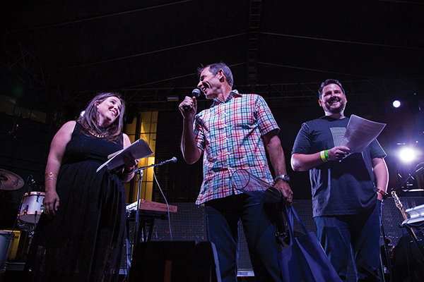Mayor John Curtis (center) is comfortable in the spotlight and at the microphone, including stage time at the Rooftop Concert Series with organizer Courtney Kendrick (left) and sponsor Devin Baer (right) of Google Fiber. (Photo by Justin Hackworth)